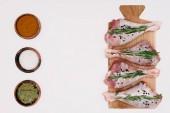 pohled shora syrové kuřecí stehna s rozmarýnem na dřevěné desce, solí, paprikou a bay listy v miskách, izolované na bílém