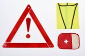 flat lay with warning triangle, first aid kit and reflective vest isolated on white