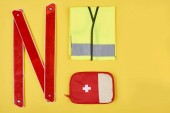 Fotografie flat lay with arranged first aid kit and automotive accessories isolated on yellow