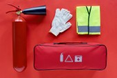 top view of automotive handbag, reflective vest, gloves and fire extinguisher on red background