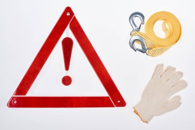 flat lay with warning triangle, gloves and car tow rope isolated on white
