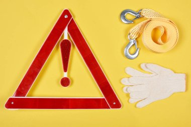 top view of warning triangle road sign, gloves and car tow rope isolated on yellow