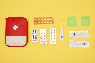 Top view of first aid kit with various medicines isolated on yellow stock vector
