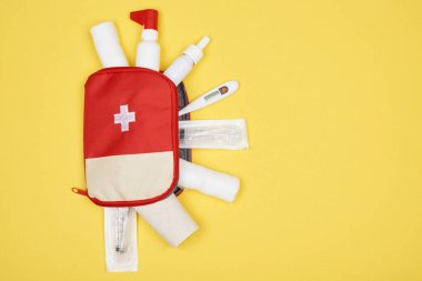 top view of first aid kit with various medicines isolated on yellow