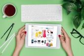 Oříznout obrázek ženské architekta drží digitální tablet s ebay na obrazovce u stolu s rozdělovačem, kávy a v květináči
