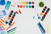 Photo top view of artist workplace with colorful paints and markers on white table