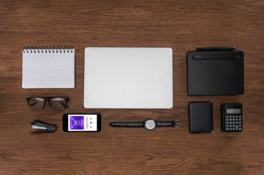 top view of workplace with arranged empty textbook, laptop, wristwatch and smartphone with apple music application on screen