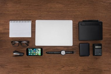 top view of workplace with arranged empty textbook, laptop, wristwatch and iphone on wooden table