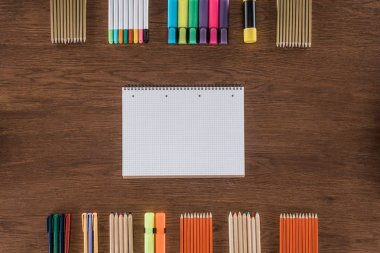 top view of empty textbook near arranged various pencils and markers on wooden table