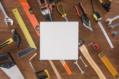 top view of empty paper near arranged various tools on wooden table