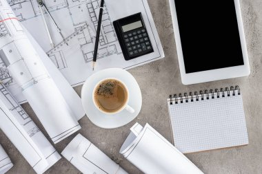 Top view of architect workplace with coffee cup, blueprints, calculator and digital tablet with blank screen stock vector