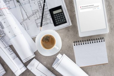 Top view of architect workplace with coffee cup, blueprints, calculator and digital tablet with blocked page of vk.com on screen stock vector