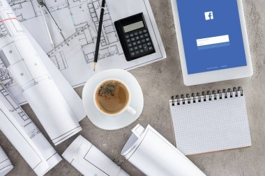 Top view of architect workplace with coffee cup, blueprints, calculator and digital tablet with facebook  on screen stock vector