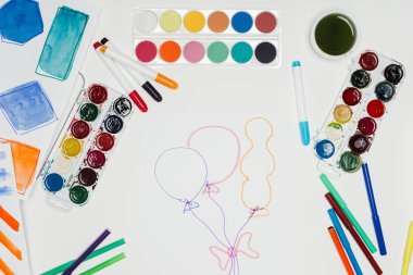 Top view of artist workplace with colorful paints, markers and painting of air balloons on white table stock vector