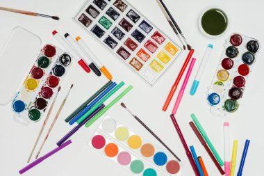 Top view of colorful paints, paintbrushes and markers on white table stock vector