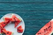 Fotografie flache Lay mit frischen Wassermelone Stücke auf Platte auf blauen hölzernen Tischplatte