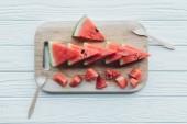 Fotografie flache Lay mit arrangierten Wassermelone Stücke auf Schneidebrett und Kunststoff Gabeln auf hölzernen Tischplatte