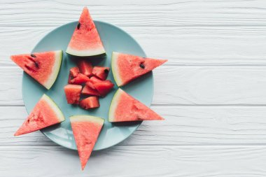 top view of fresh watermelon pieces on plate on white wooden surface