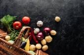 plochý ležela s různými čerstvá zelenina v košíku na černý mramorový stůl