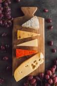 Fotografia vista superiore di formaggi assortiti sul tagliere di legno con luva su superficie scura