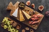Draufsicht der sortierten Käse und Früchte auf dunkle Tischplatte