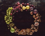 Fotografie flat lay with various fruits, bread pieces and hazelnuts assorted in circle on dark tabletop