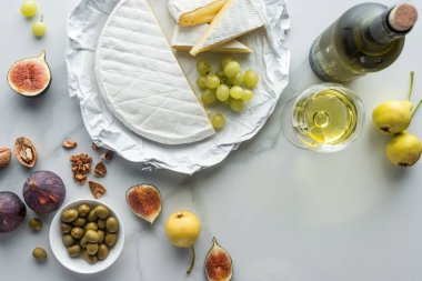 Flat lay with olives, camembert cheese, wine and fruits arranged on white marble surface stock vector