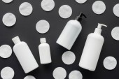 pohled shora rozptýlené lahví ze smetany a kosmetické vatové polštářky izolované na černou, koncepce krásy