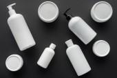 pohled shora rozptýlené bílé lahví krém izolované na černou, krása konceptu