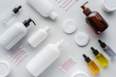 flat lay with bottles of cream, natural oils and cosmetic pads on white surface, beauty concept