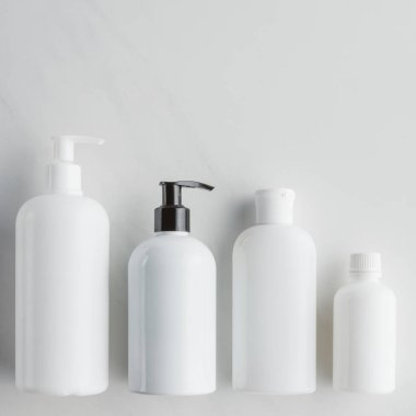 top view of four white bottles of cream on white surface, beauty concept