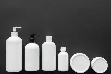 top view of white plastic bottles of cream isolated on black, beauty concept