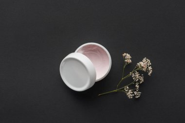 top view of bottle of cream and dried flowers isolated on black, beauty concept