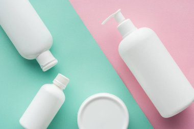 top view of bottles of cream on green and pink surface, beauty concept