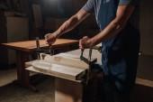 Fotografie cropped shot of carpenter in apron working on wood at workshop