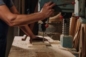 Fotografie partial view of woodworker using electric drill on wood at workshop