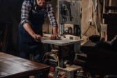 partial view of woodworker using electric drill on wood at workshop