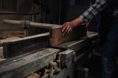 Fotografie Oříznout záběr tesaře pracujícího se dřevem v dílně
