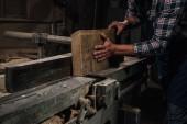 Oříznout záběr tesaře pracujícího se dřevem v dílně