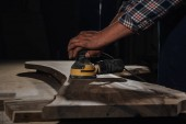Fotografie partial view of carpenter working with electric plane at workshop
