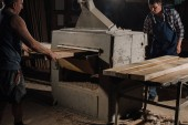 carpenters working with wooden planks at wooden workshop
