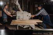 Fotografie carpenters working with wooden planks at wooden workshop