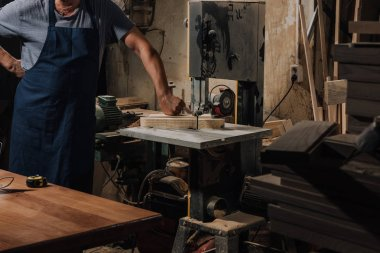 partial view of woodworker standing near electric drill at wooden workshop