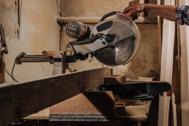 partial view of carpenter using circular saw at wooden workshop