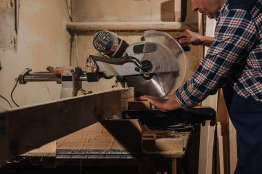partial view of carpenter using saw at wooden workshop
