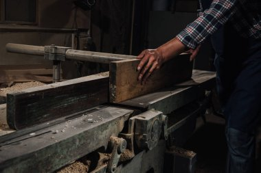 cropped shot of carpenter working with wood at workshop