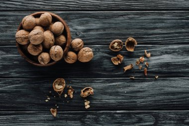 organic walnuts in wooden bowl on dark wooden table