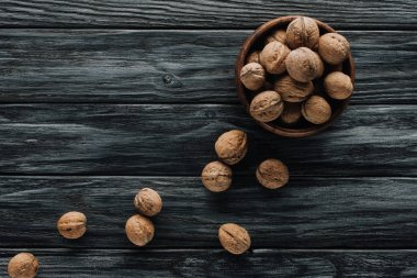 delicious walnuts in wooden bowl on dark wooden tabletop