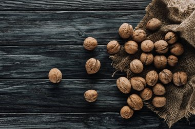 walnuts in nutshells with sackcloth on dark wooden surface