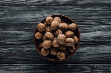 walnuts in wooden bowl on dark wooden background